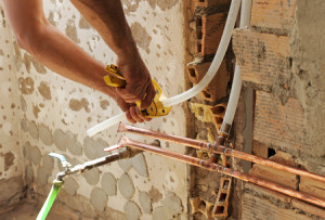 60749884 - plumber connecting pvc pipes with copper pipes