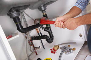 45779729 - plumber with plumbing tools on the kitchen. renovation.